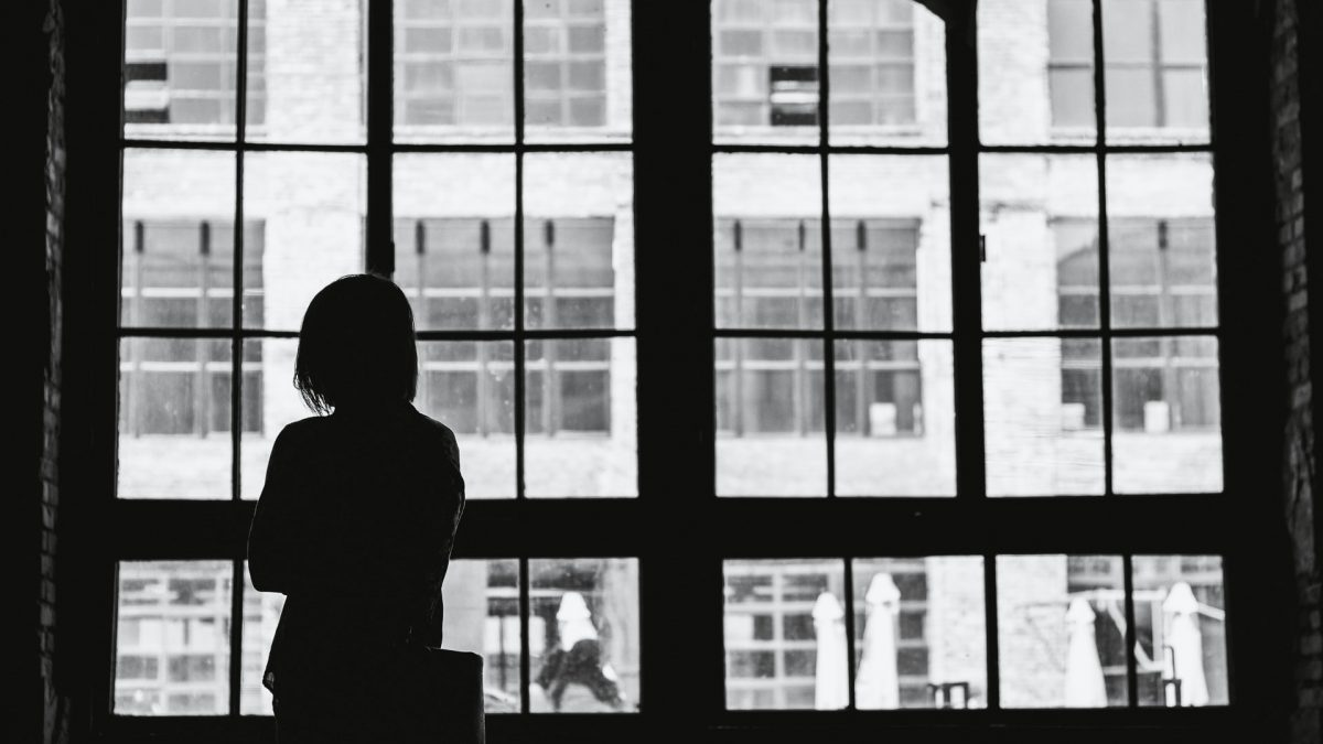 A woman stares out a large window that looks out over a cityscape