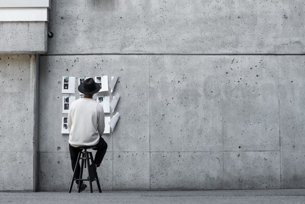 A Black man in a white sweatshirt sits on a stool facing a huge cement wall