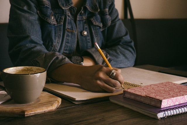 A Black woman in a denim jacket writes notes in a journal