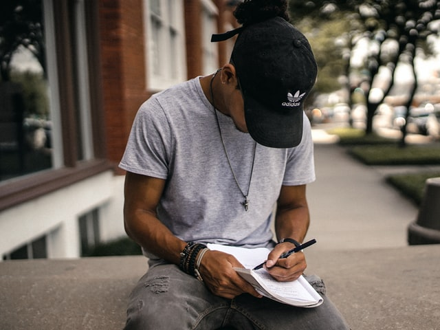 A Black mean wearing a hat writes in a notebook