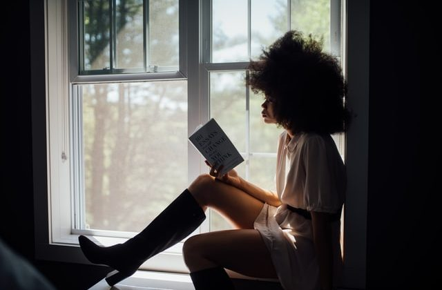 A Black woman sits on a window sill and reads a book of essays