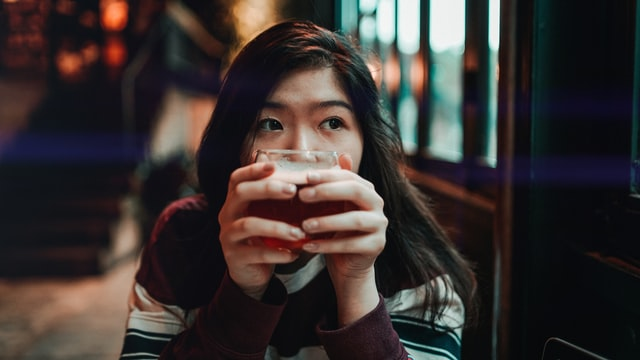 An Asian woman holds a cup of tea in front of her face and glances to the side